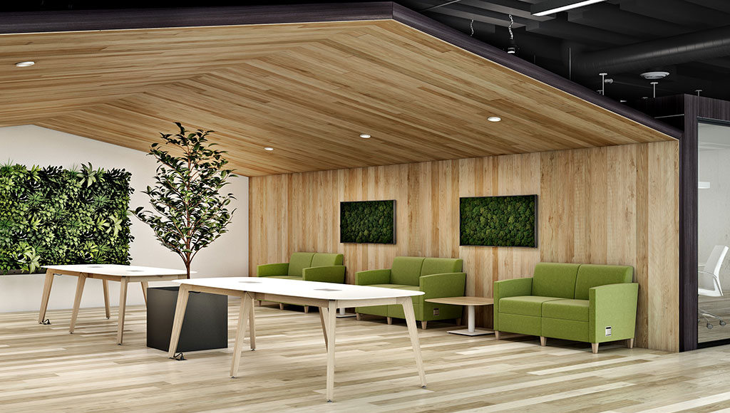 Waiting area space with three couches, two tables and a tree, green foliage on the walls as well